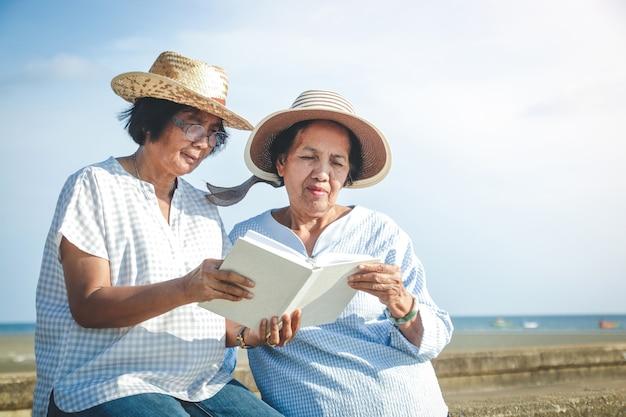 Две азиатские пожилые женщины сидят на пляже и читают книгу