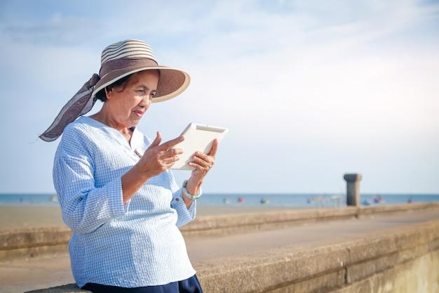 高齢のアジア人女性がタブレットを介してインターネットで遊んでリラックスし、海を訪れます。