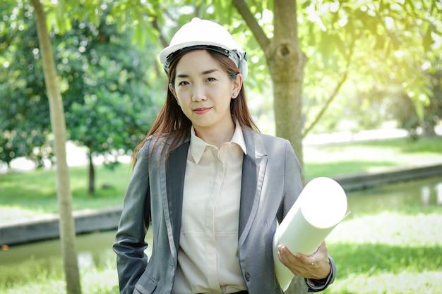 女性環境エンジニアは、紙製の帽子をかぶって、建設の実現可能性を研究しています。