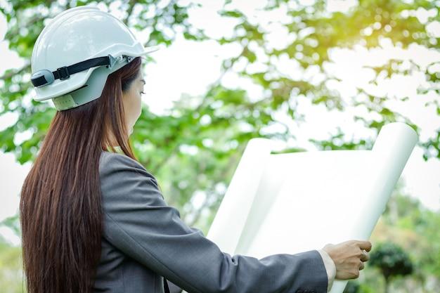Женский инженер-эколог в костюме, в белой шляпе, стоя с бумажным планом