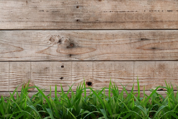 Светло-коричневый деревянный фон с зеленой травой