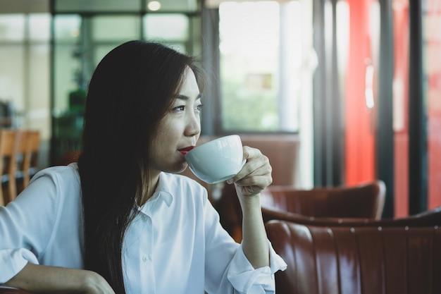 美しい若い働く女性、ドリンクショップで午後のコーヒーをすすりながら