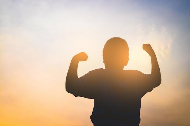 Мальчик поднял обе руки, чувствуя себя энергичным по утрам. силуэт