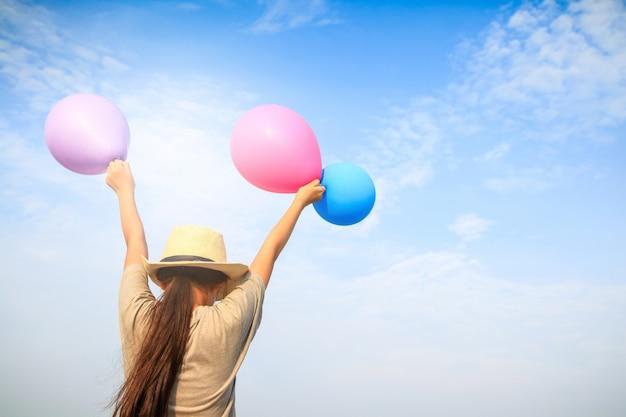 女の子は、青、ピンク、紫の風船を持っています。空に腕を上げた