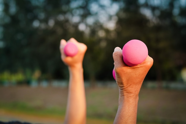 Пожилые люди держат в руках розовые гантели для занятий спортом в саду.