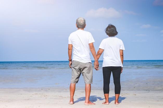 ビーチで海を見るために手を繋いでいる老夫婦