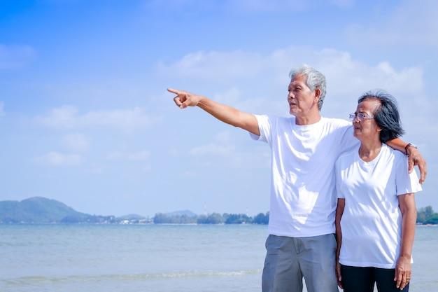 Пожилая азиатская пара носит белую рубашку. они пошли на пляж. он стоял, обнимая друг друга и указывая пальцем на море.