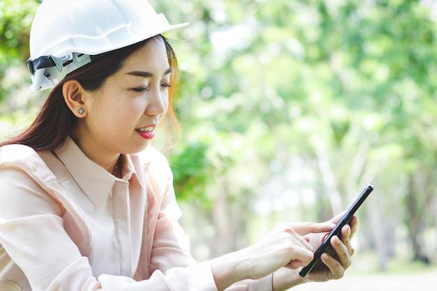 白い安全ヘルメットを身に着けているエンジニアとして働く美しい女性携帯電話を押して電話をかけます。