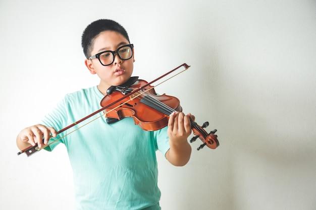 Маленький азиатский мальчик играет и практикует скрипку в белой комнате.