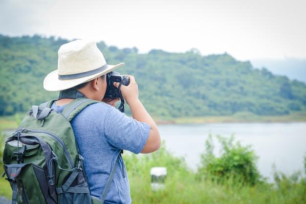 帽子をかぶった小さなアジアの少年は、自然への旅行が好きです。カメラをかざして風景写真を撮ります