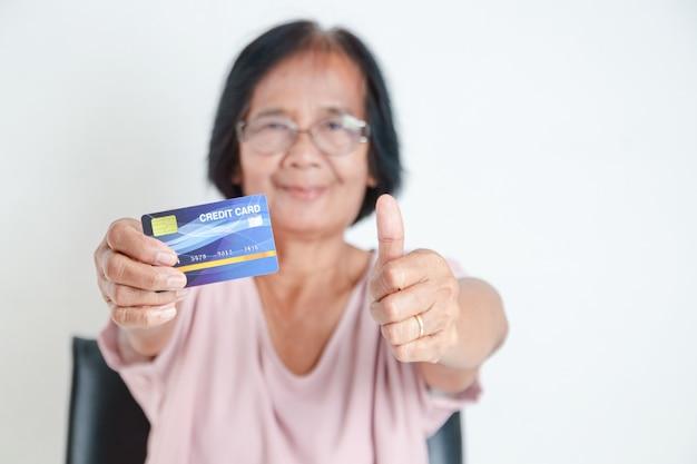 シミュレートされたクレジットカードを持っている高齢のアジアの女性は本物ではありません。