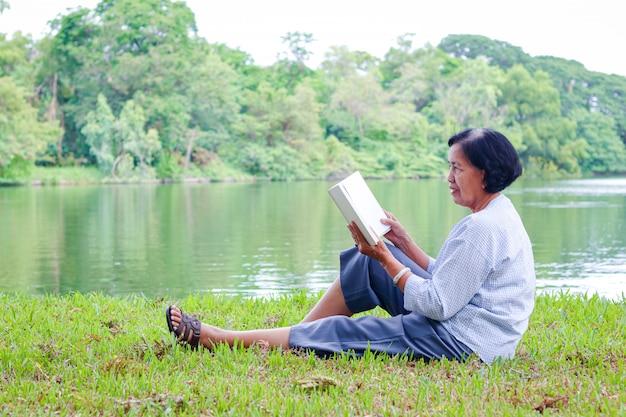 Пожилая женщина сидит и читает книгу в парке счастливая жизнь после выхода на пенсию