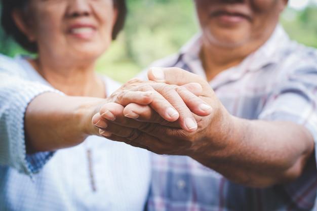 Пожилые влюбленные, держась за руки, танцуют в саду развлекайся на пенсии. концепции старшего сообщества