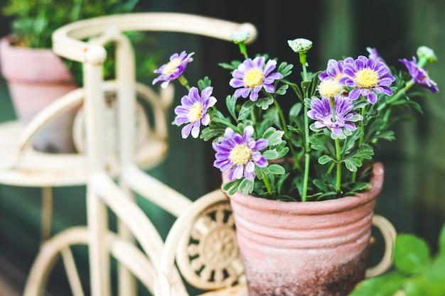 紫色の花は粘土の鉢に入っています。スチール自転車に乗る