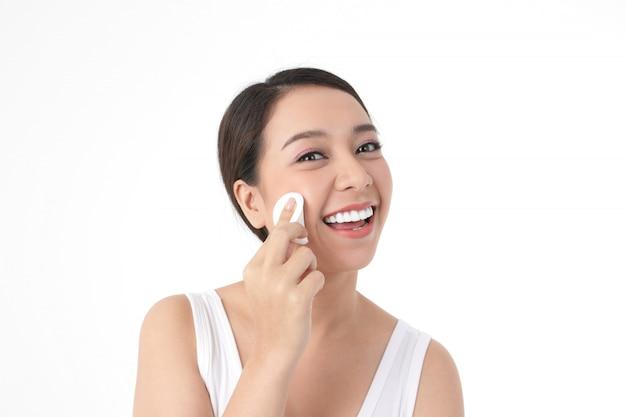 美しいアジアの女性の皮膚の治療、スポンジを使用して顔を拭く、美容、笑顔で魅力的。