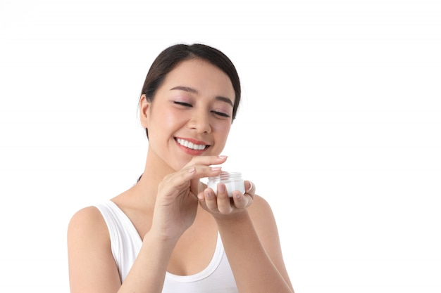 Азиатская женщина любит здоровье, имеет светлую кожу, чистую и красивую, наносит крем для тела белого цвета.
