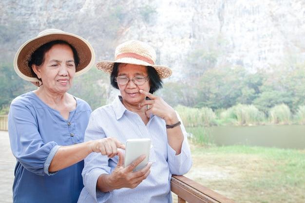 Старшая азиатская женщина держит смартфон, делает фотографии и играет в социальные сети. она наслаждается выходом на пенсию. концепция пожилого сообщества. копировать пространство