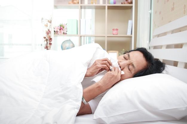 寝室のベッドで高齢者の女性