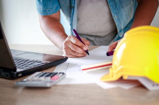 アジアの男性が建設作業中紙に情報を書き込むためにペンを持ちます。
