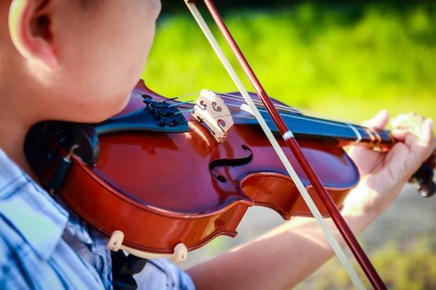 アジアの少年がバイオリンを弾く