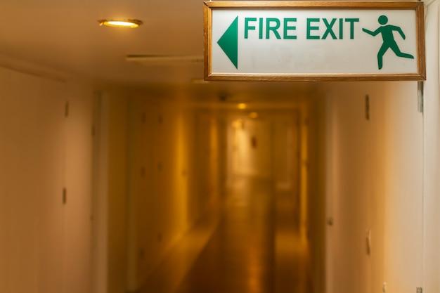コピーを挿入するための空の白いスペースがあるマンションの背景の中のぼやけた長い散歩道の非常口サインに焦点を当てます。ワームトーンの照明が付いているホテルの廊下にあるファイアエスケープ方向棒。