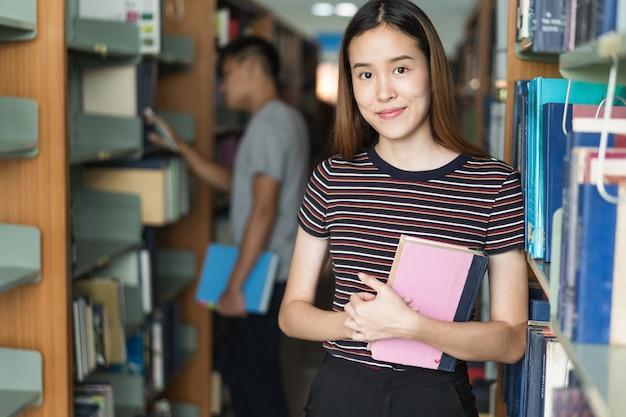 若い女の子は図書館で本を読みます。