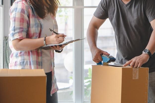 Женщина проверяет вещи в картонной коробке перед отправкой в транспортную компанию и переезжает на новое место квартиры.