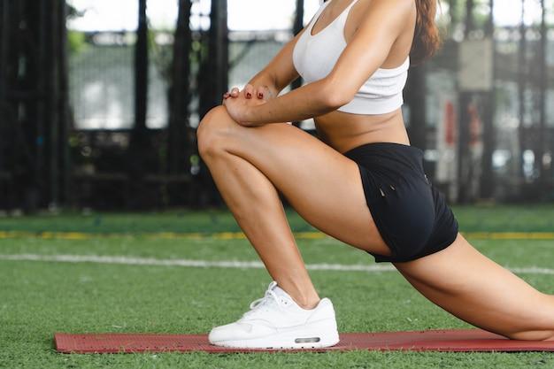女性は運動する前にウォームアップのためにストレッチします。