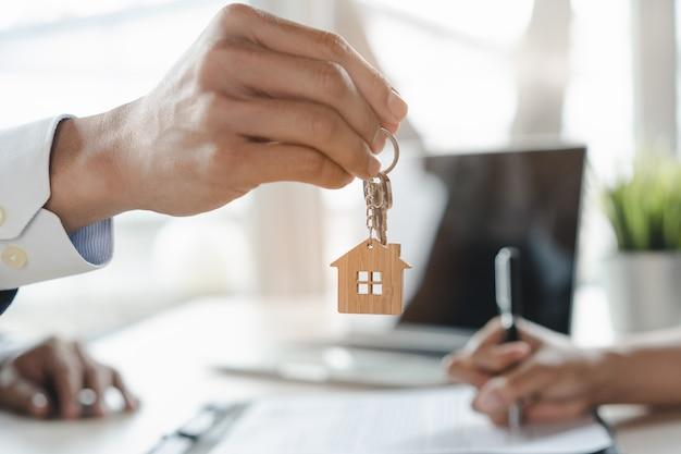 Закройте вверх по взгляду домашние ключи в руке агента давая к новому владельцу.