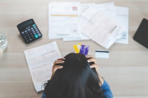 クレジットカードの負債を支払うためにお金を見つけることを試みている強調した若いアジア女性のトップビュー。セレクティブフォーカスを手に。
