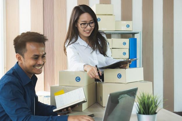 中小企業の経営者が注文を確認し、製品の箱を準備する。