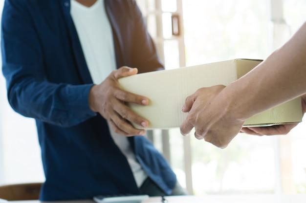 郵便配達人が荷物を受け取り人に配達する。
