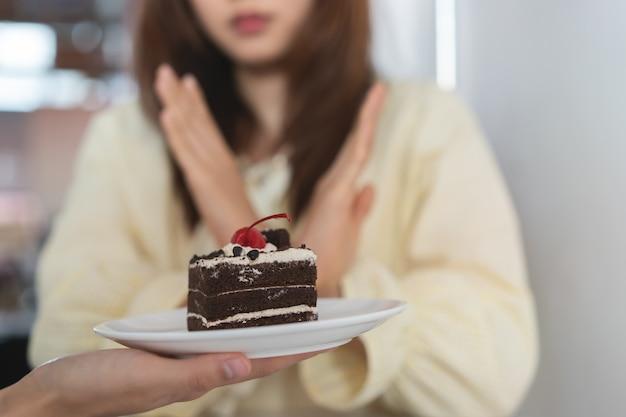 Девушке запрещают есть сладкое или пирожное во время диеты.