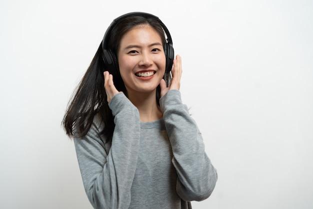 幸せなアジアの若い女の子が白い背景で隔離のヘッドフォンから音楽を聴きます。