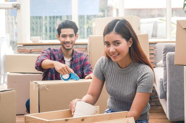 Женщина и мужчина распаковывают грязные коробки после переезда