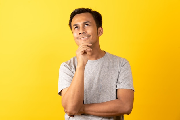 Азиатский мужчина думает и улыбается