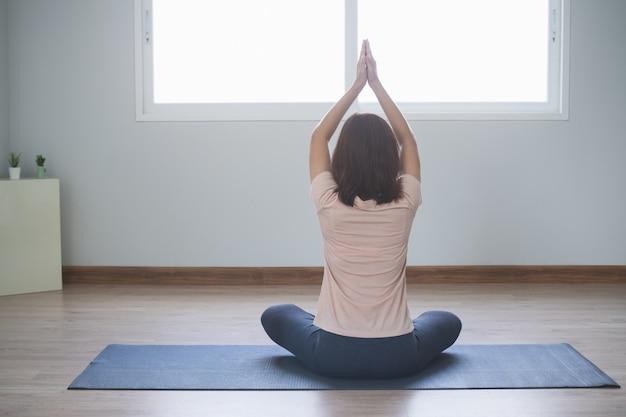ヨガと瞑想のライフスタイル。自宅のリビングルームでヨガを練習する若い美しい女性の背面図。