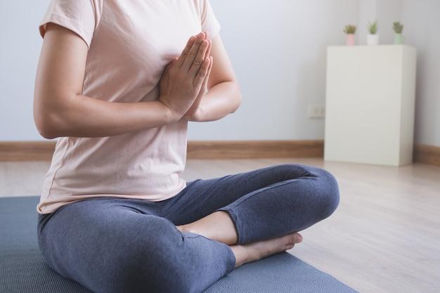 ヨガと瞑想のライフスタイル。自宅のリビングルームでヨガのナマステのポーズを練習して若い美しい女性のビューを閉じます。
