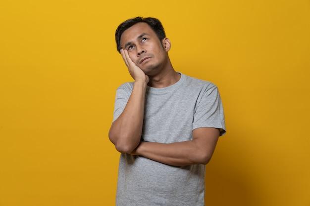 落ち込んでいるアジアの若い男は失敗を感じて下向き。黄色の背景に分離されたスタジオで撮影します。
