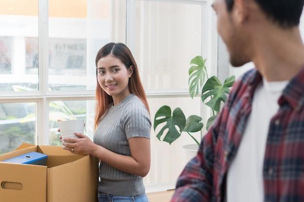 Женщина и мужчина распаковывают грязные коробки.