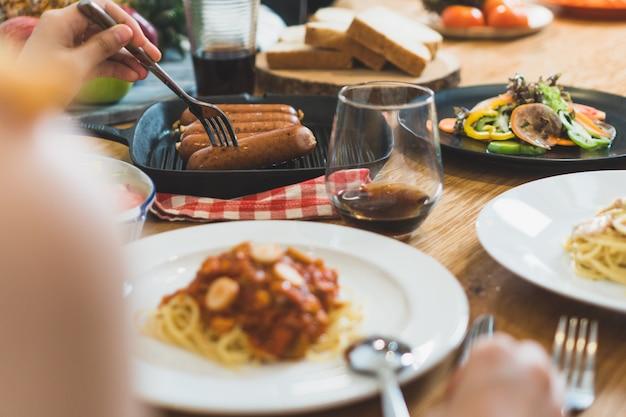 木製のテーブルの上に食べ物や友達一緒に夕食を食べての様々な。