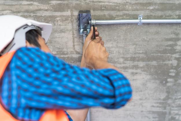 電気技師は電気を配線する準備をします。