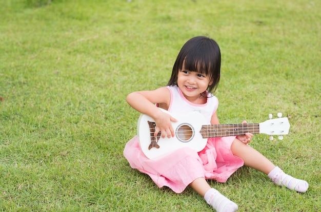 Симпатичные азии маленькая девочка, сидя и играя гавайской гитаре на зеленой траве