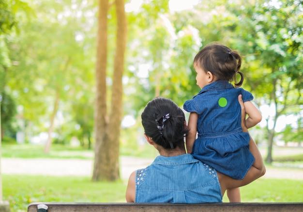 母と娘が公園に戻って座っている、娘は彼女の母の肩に座っています。