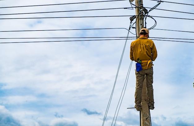 技術者は電気問題を修理するために電柱に登っています。