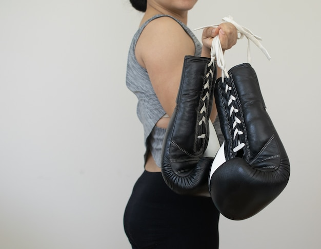 女は運動を行うためにブラックボクシンググローブを運ぶ