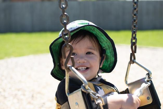 太陽の日にスイングをするとき、小さな男の子は非常に美しい笑顔を持っています