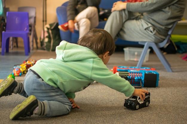 Маленький мальчик играет в машины на полу, а взрослые сидят и разговаривают