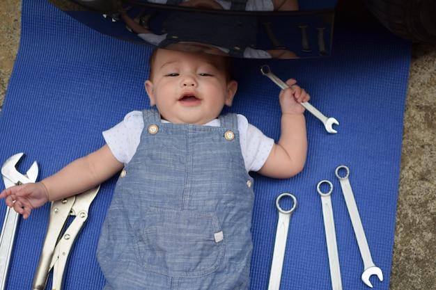赤ちゃんは機械的な役割を果たす、彼の背中に多くのツールで車を修正するために横たわる