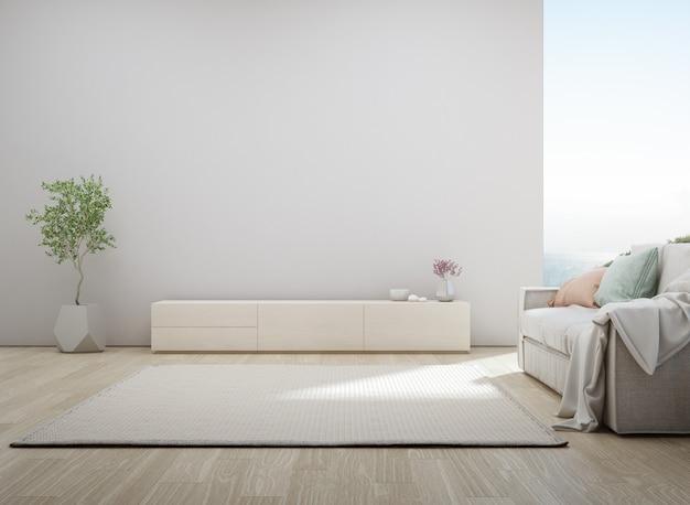 Гостиная с видом на море роскошного летнего пляжного домика с подставкой под телевизор и деревянным шкафом.
